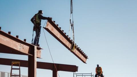Construction workers lower a steel beam into place.